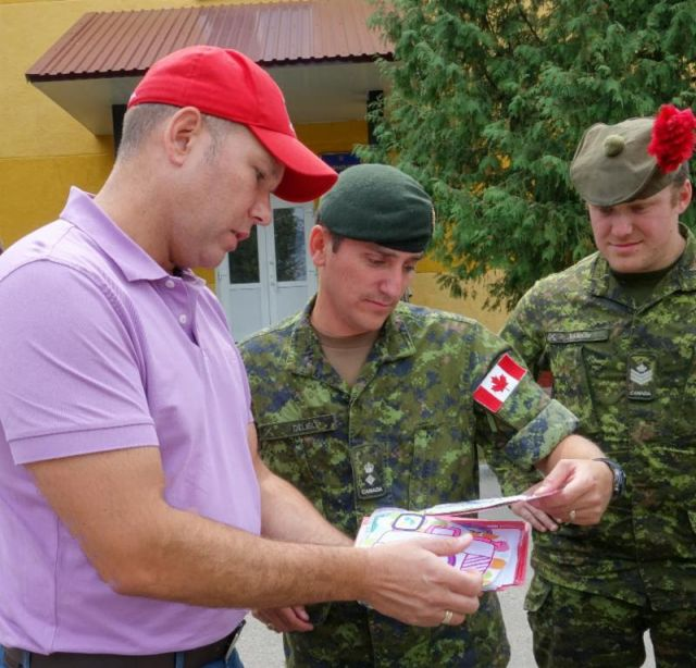 Paul Grod gifting a Canadian flag signed at the Help Us Help the Children camp by Ukrainian orphans and children of soldiers who perished in the ATO